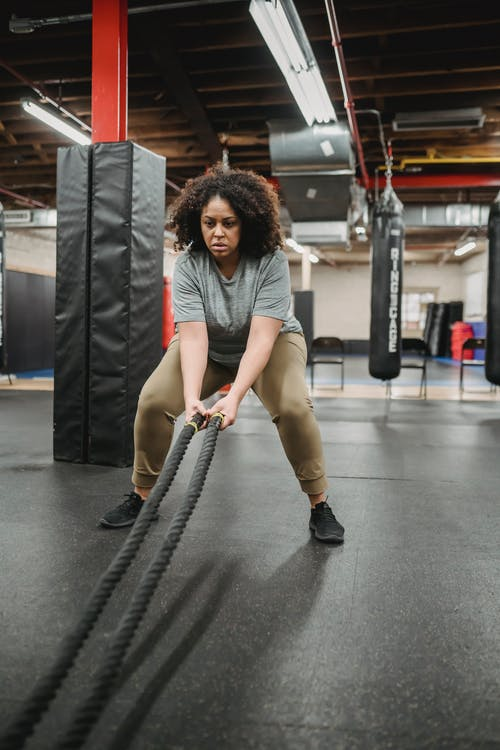 Full body focused African American female in sportswear exercising with battle ropes during functional workout in contemporary fitness center