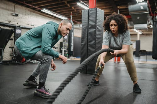 Determined black woman exercising with battle ropes near coach