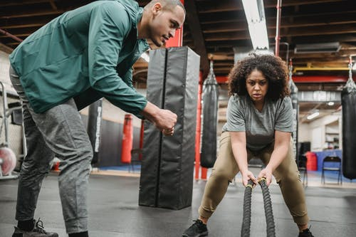 Focused plump African American female in sportswear performing battle ropes exercise near fit male coach in modern gym