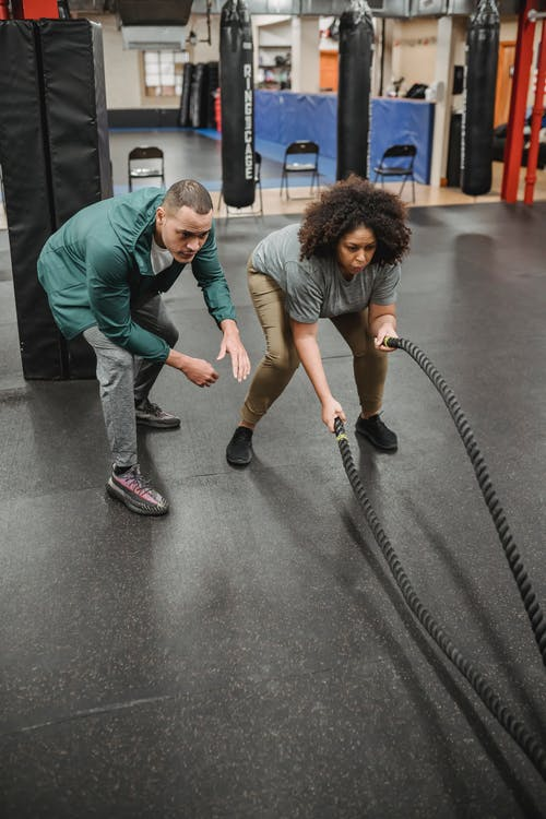 Strong male coach instructing black woman exercising with battle ropes