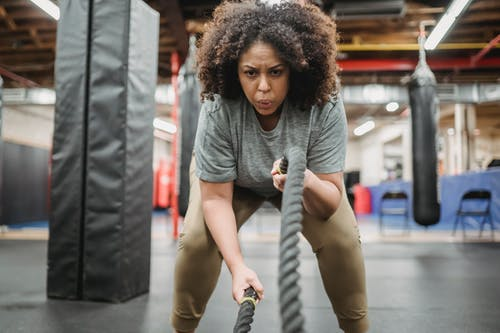 Determined black woman exercising with battle ropes in gym