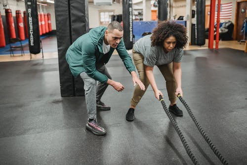 Full body focused African American female in activewear exercising with battle ropes near professional male instructor in contemporary fitness center