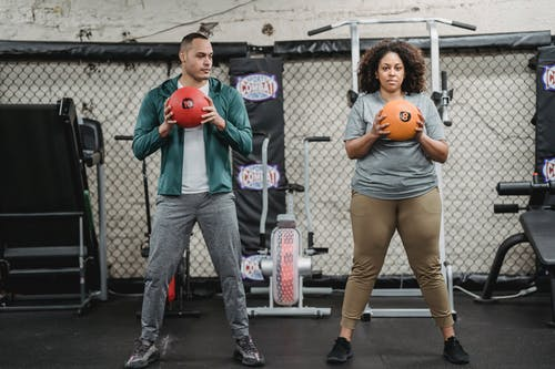 Fit male instructor with ball showing exercise to black woman