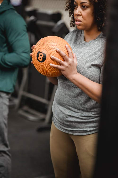 Crop determined plump African American female in sportswear exercising with fitness ball in modern gym