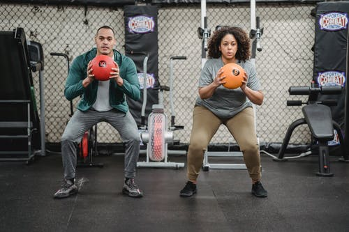 Full body sporty ethnic male coach and plus sized African American female in activewear squatting with fitness balls in hands in modern gym
