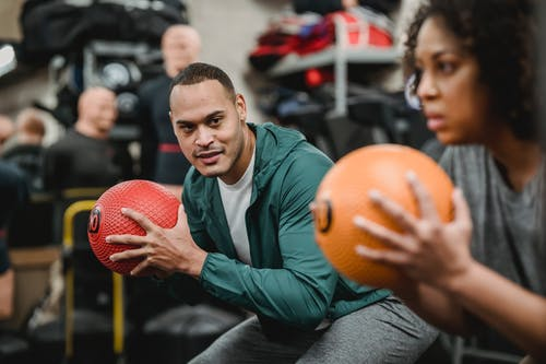 Diverse coach and female trainee squatting with fitness balls