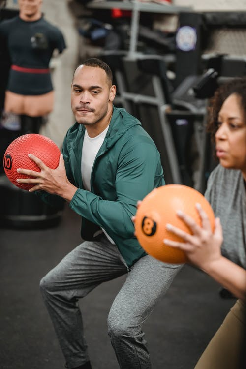Concentrated young ethnic male trainer doing squats exercise with weight ball near crop African American female in gym