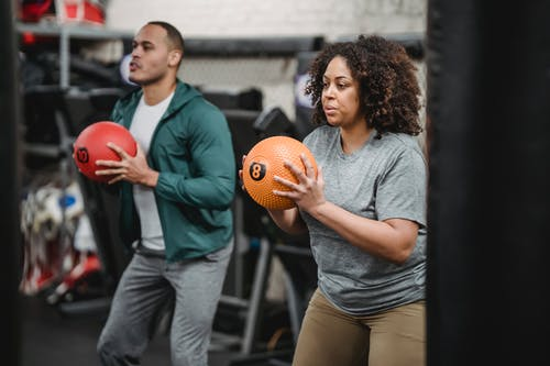 Concentrated young diverse trainer and athlete exercising with medicine balls in gym