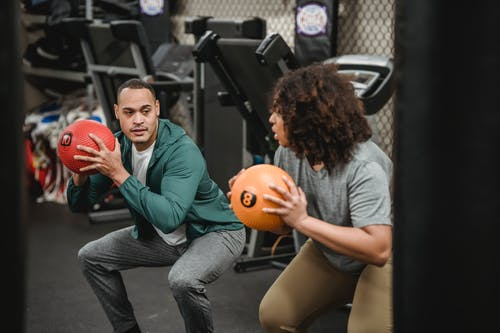 Determined multiracial athletes looking at each other while doing squats with balls