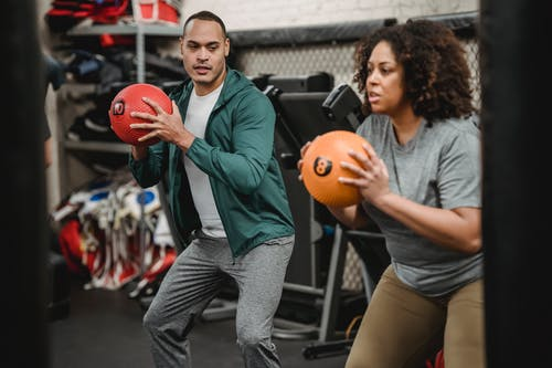 Serious young ethnic male instructor in sportswear looking at plus size African American female doing squat exercise with medicine ball in gym