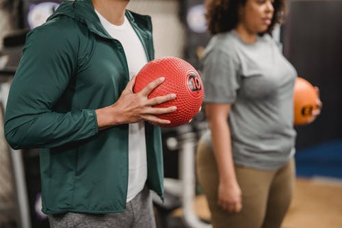 Anonymous man with ethnic woman standing in gym during training with balls