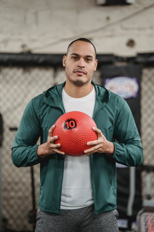 Confident young ethnic male athlete in sportswear holding medicine ball in hands and looking at camera while training in gym