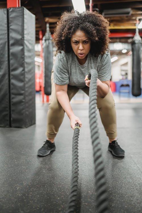 Strong obese black woman exercising with heavy ropes in gym