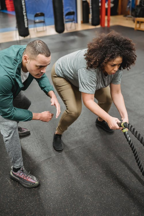 From above of concentrated young male trainer instructing determined obese African American woman doing exercise on battle ropes during functional workout in gym with