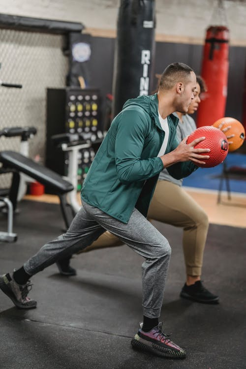 Side view of sporty young multiethnic male trainer and female client doing forward lunges exercise with medicine ball during workout in gym together