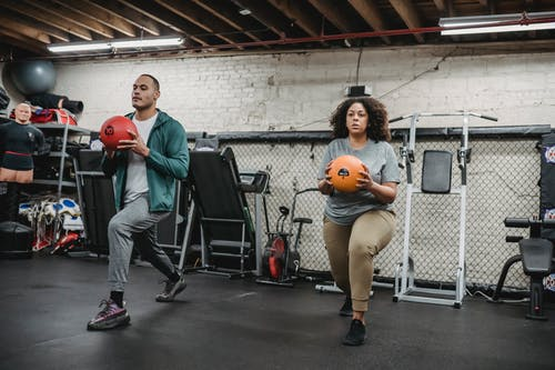 Young multiracial man and woman doing lunges exercise with weight balls in gym