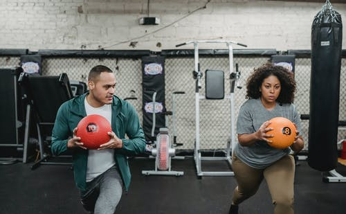 Young muscular ethnic male instructor in activewear doing lunges exercise with ball near plus size black woman during training in sport club
