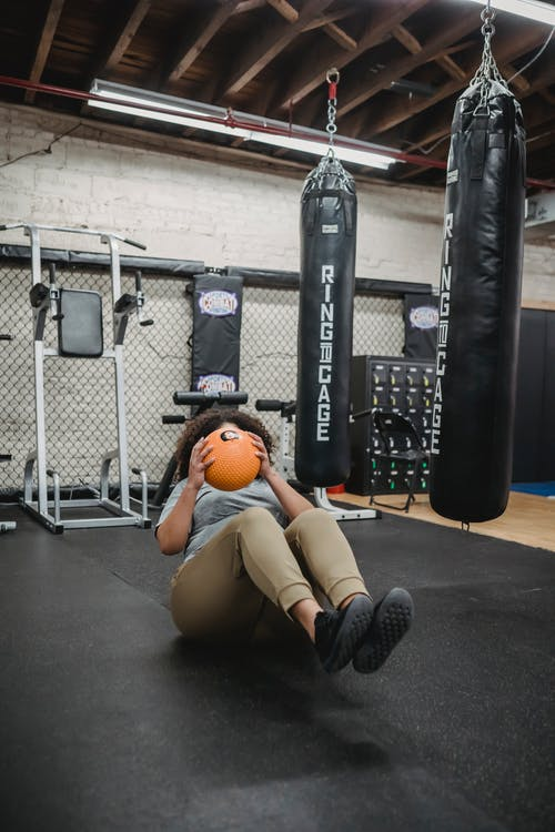Obese black woman doing crunches with weigh ball in gym