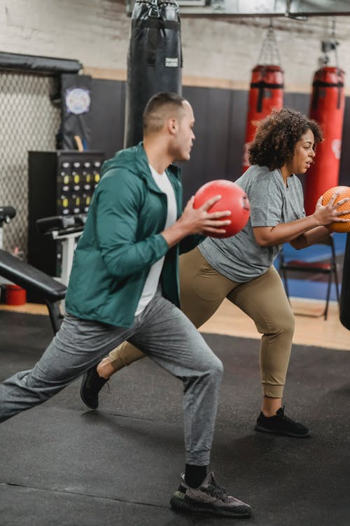 Side view of fit young ethnic male couch instructing focused obese African American lady doing lunges with medicine ball in gym