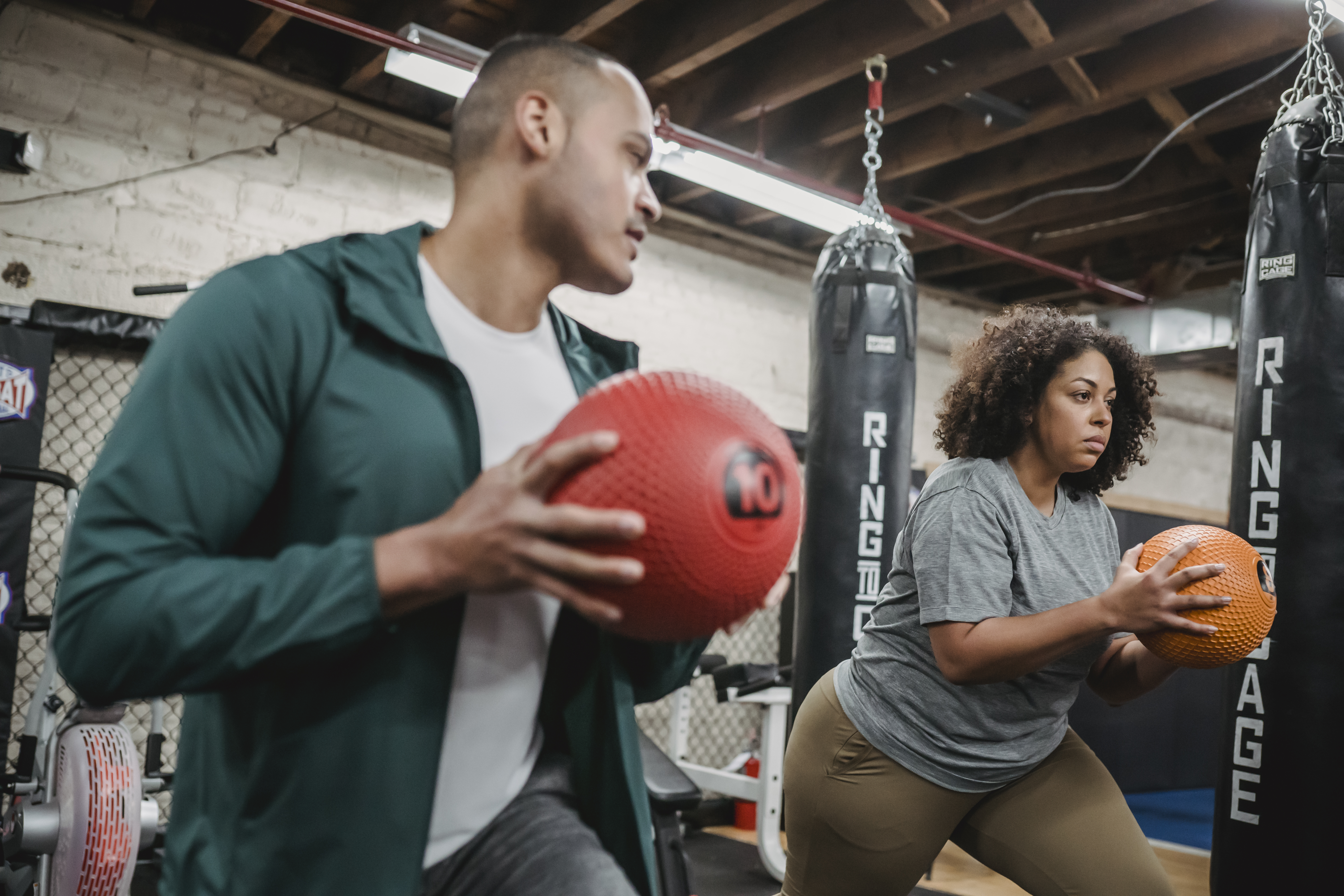 multiethnic young man and woman doing butt exercise with weigh balls in gym