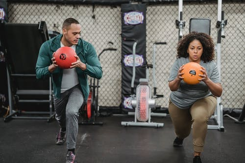 Multiethnic fit man and obese woman with medicine ball doing lunges in sports club