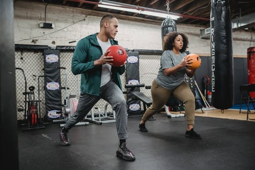 Full body of experienced instructor doing exercises with African American overweight woman in gym