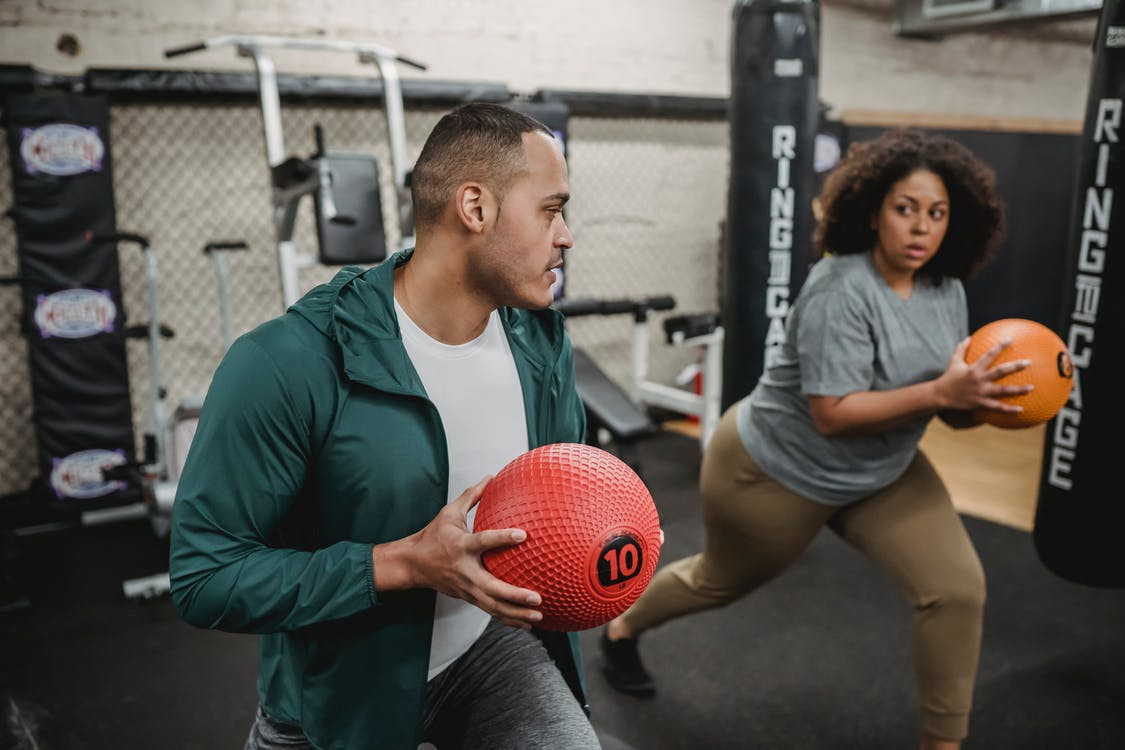 Coach and plus size black woman training with ball