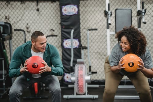 Diverse man and plump woman exercising with bright balls in sport club with gym equipment
