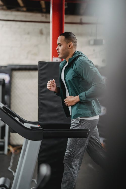 Side view of focused male in activewear jogging on treadmill in modern sport club