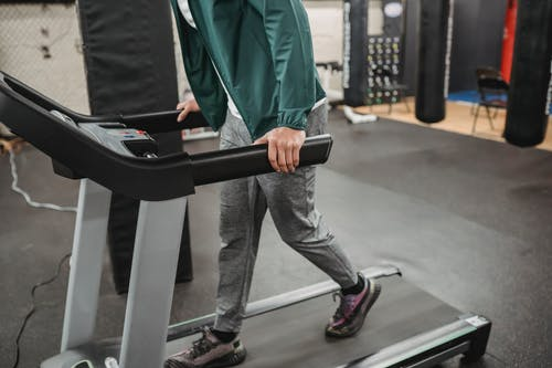 Crop anonymous male walking on contemporary treadmill in modern sport club with gym equipment