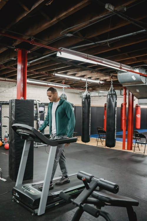 Full body of male in activewear on treadmill in sport club with punching bags