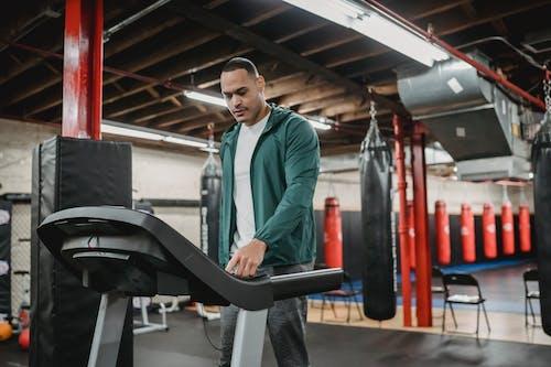 Man regulating speed on modern treadmill