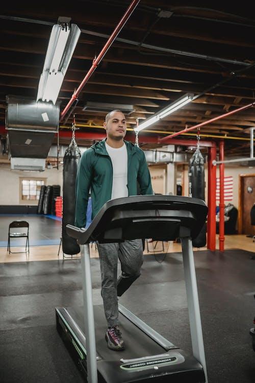 Full body of fit male in sportswear exercising on treadmill in modern sport club