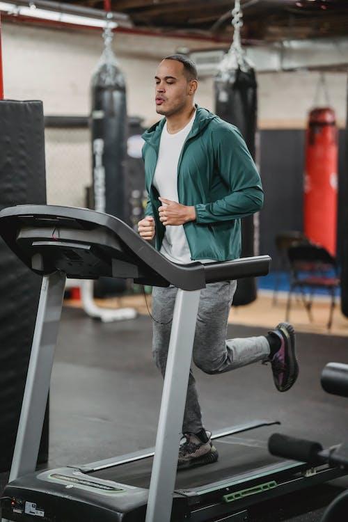 Fit focused man running on treadmill in sport club