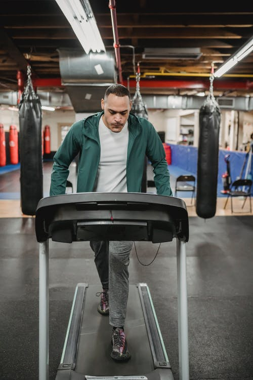 Energetic man walking on treadmill in gym