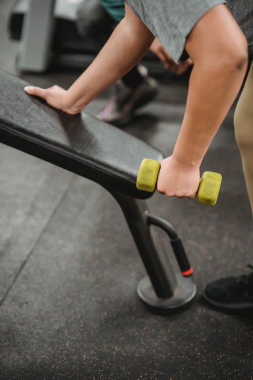 Crop anonymous female exercising with gym equipment and lifting dumbbell on blurred background