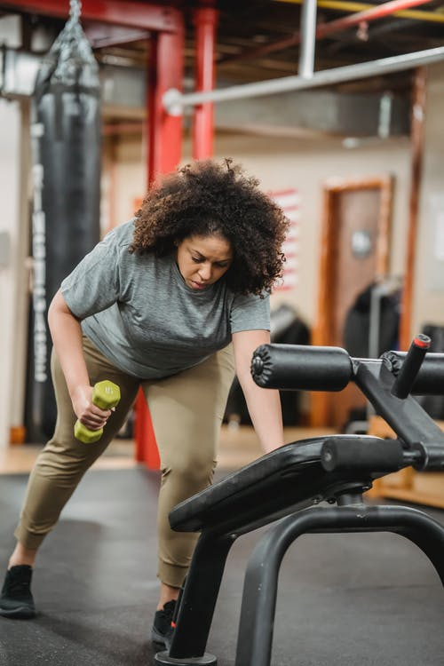 Full body of African American female training with dumbbell and gym equipment in contemporary sport club