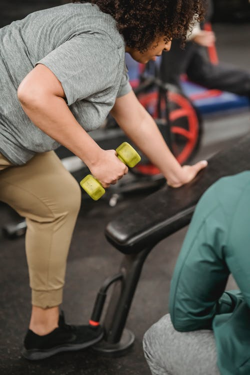 Black woman exercising with dumbbell while trainer watching