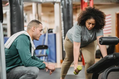 Multiethnic man and woman training together in gym