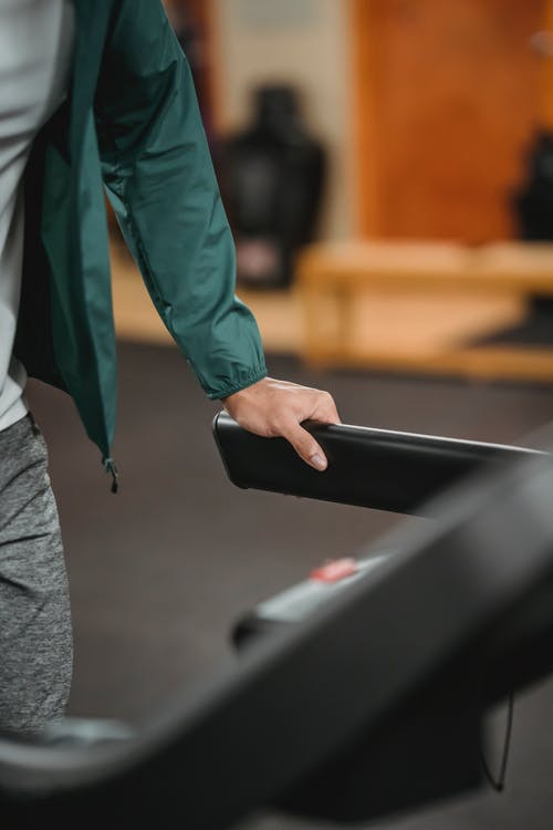 Man using treadmill while jogging in gym
