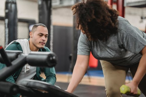 Experienced instructor watching anonymous African American female lifting dumbbell on blurred background of gym