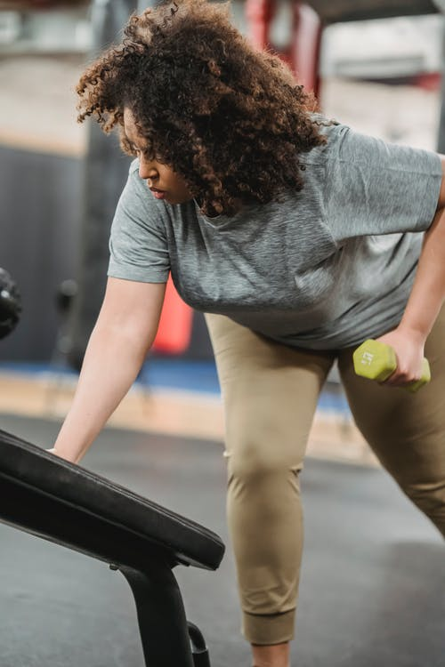 Plus size black woman with dumbbell leaning on gym equipment