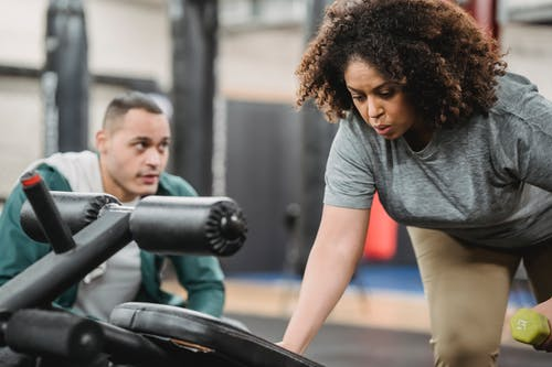Professional instructor encouraging black woman lifting dumbbell