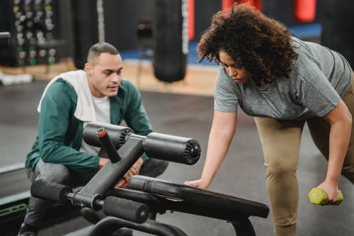 Focused instructor helping plus size African American female doing exercises with dumbbell near gym equipment