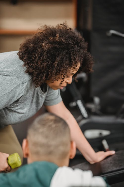 Professional anonymous coach watching African American enduring female doing exercises with dumbbell on blurred background of gym