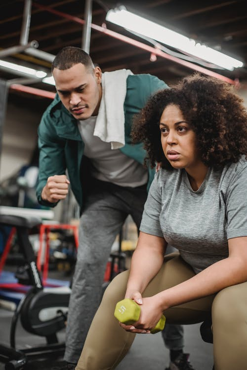 Serious African American female sitting with dumbbell and listening to instruction of personal trainer in gym