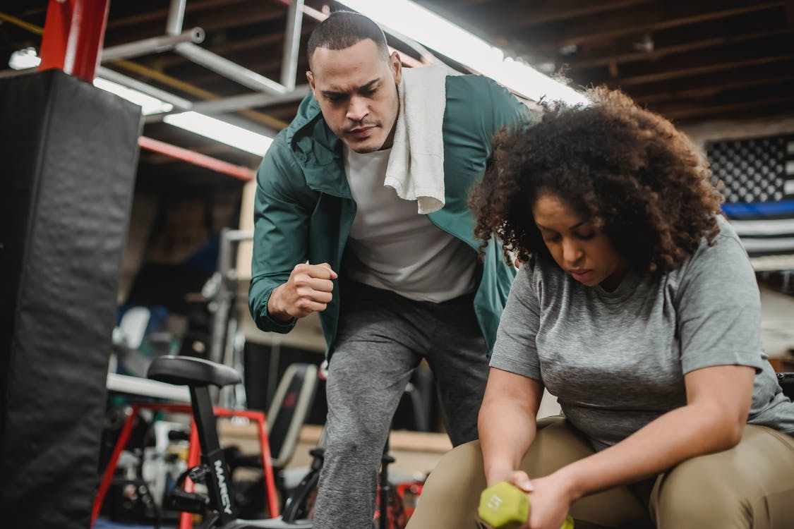 African American trainer working with black female client during training in modern gym