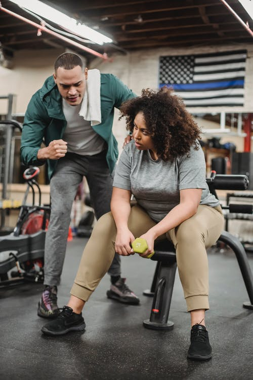Black woman with personal trainer in gym