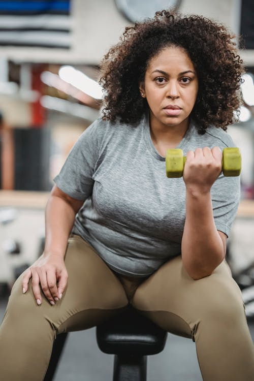 Overweight black woman lifting dumbbell in gym