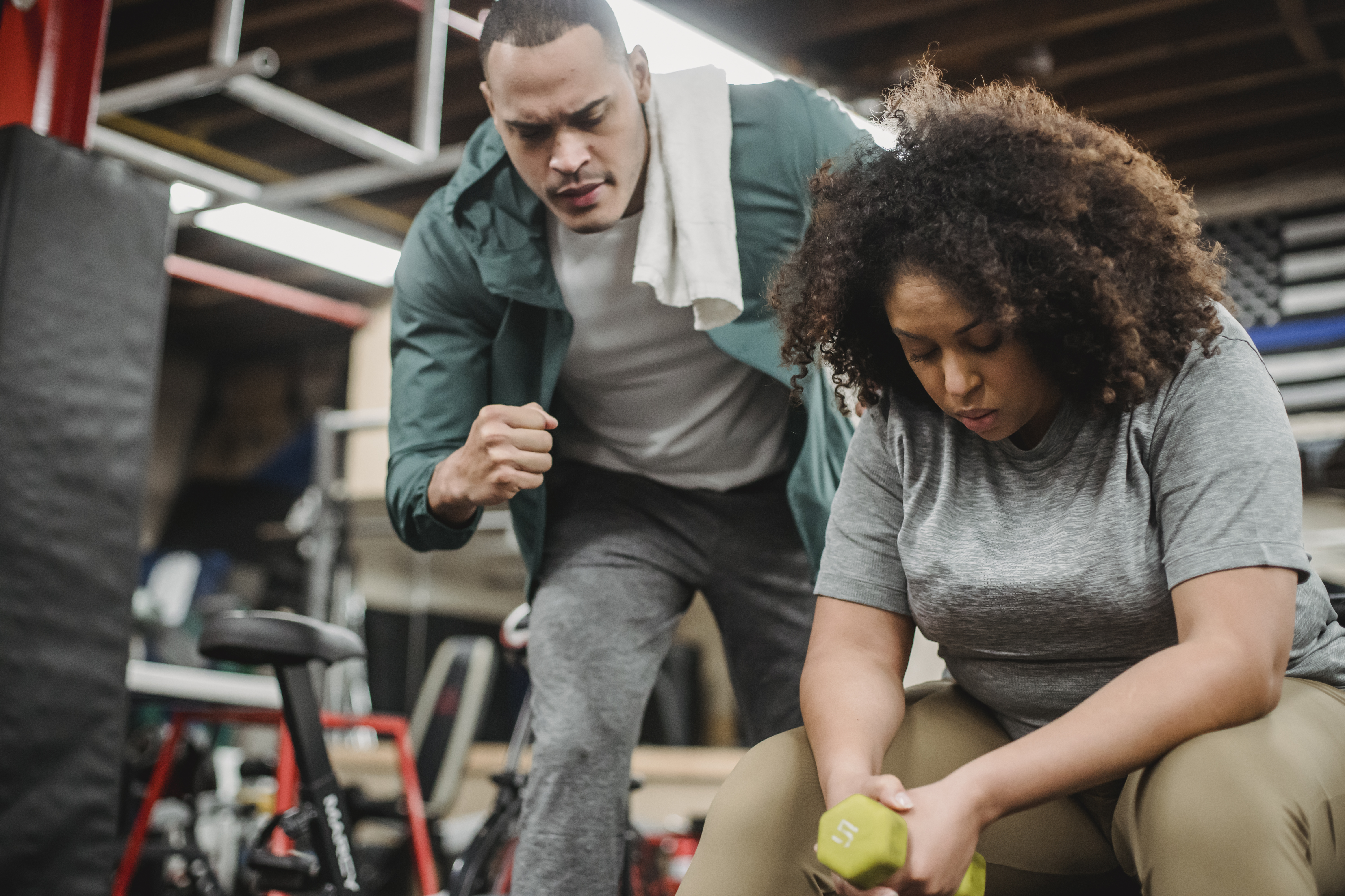 black trainer teaching woman doing dumbbell exercise correctly